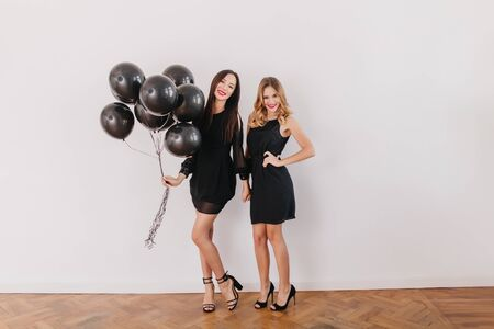 Full-length portrait of slim caucasian girls in black dresses preparing for birthday party. Graceful brunette lady wears sandals holding helium balloons while posing with sister in her room.