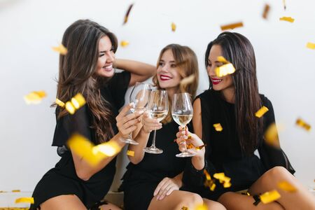 Cheerful black-haired woman with red lips looking at wineglass and smiling. Indoor portrait of excited girls having fun at hen-party and joking under sparkle confetti.