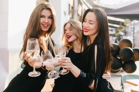 Portrait of three sisters in black outfit celebrating important event with champagne. Inspired long-haired woman looking away while clink glasses with friends in city background.