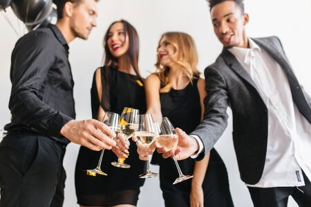 Indoor portrait of brunette girl clink wineglasses with friends and looking at brunette guy. African man in stylish white shirt having fun at home party and enjoying champagne. 免版税图像
