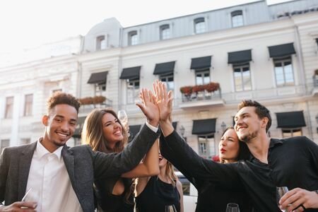 Happy friends clap their hands and laughing, enjoying summer evening in city. Outdoor portrait of inspired african man in trendy jacket drinking champagne with girls n front of old building.