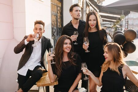 Gorgeous female model with romantic hairstyle dreamy looking away, holding glass of wine. Outdoor portrait of cheerful european students spending time with african friend. 免版税图像