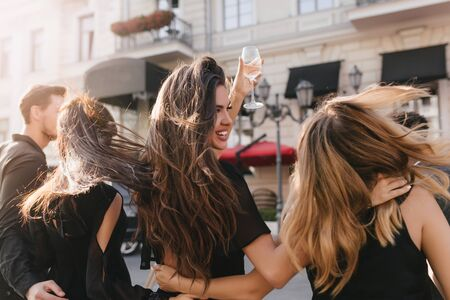 Portrait from back of joyful girls walking around town in windy day and smiling. Brunette woman with long hair waving raising wineglass and looking away, embracing friends.