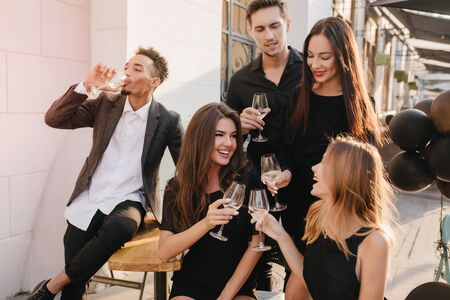 Adorable brunette lady with white manicure clink glasses with friends, celebrating birthday in cafe. Outdoor portrait of stunning girls spending time with boyfriends in weekend. 免版税图像