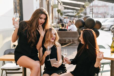 Surprised elegant woman covering mouth with hand, while looking at phone screen during party. Outdoor portrait of laughing curly european girl with smartphone drinking wine with friends. 免版税图像