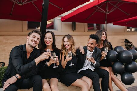 Laughing guy with short dark hair clink glasses with his girlfriend during rest in cafe. Smiling friends enjoying champagne after workday, chilling in outdoor restaurant.