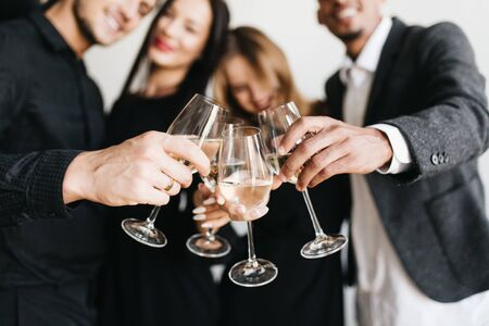 Indoor portrait of romantic blonde girl chilling at friends party and posing with glass full of champagne. Relaxed young people in stylish outfit drinking wine during meeting and joking.