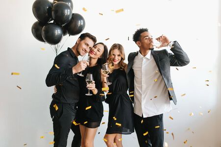 Indoor portrait of romantic pale girl with shiny curls enjoying wine with friends. Ladies in black dresses having fun at party with guys and dancing under confetti.