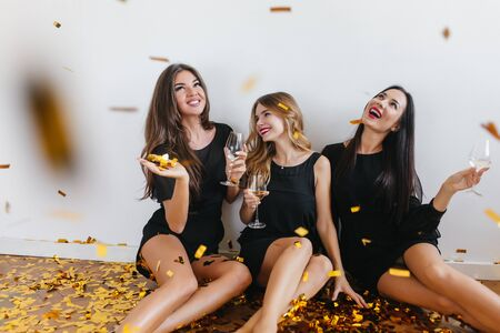 Indoor portrait of three ecstatic girls having fun at home party and looking at falling confetti. Pretty ladies in elegant black dresses enjoying champagne while sitting on the floor.