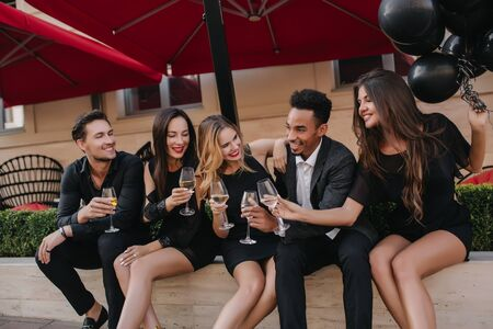 Joyful man wears black shoes looking with excited smile at his friends, sitting beside and drinking wine. Portrait of laughing people with glasses of champagne talking around in outdoor cafe.
