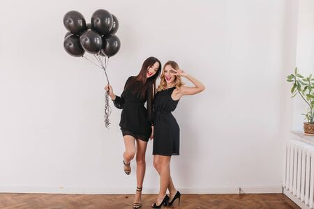 Excited brunette girl in stylish high heel shoes standing on one leg and holding balloons. Full-length indoor portrait of blonde lady in black dress posing with best friend at party. 写真素材