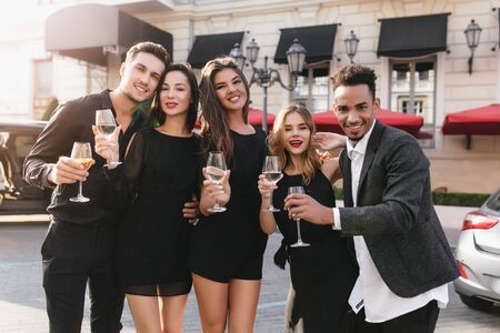 Charming woman with beautiful smile holding wineglass in front of store. Outdoor photo of glad brunette man standing beside girlfriend during photoshoot with friends.
