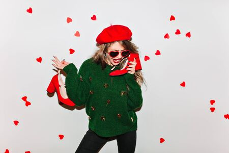 Stunning girl in red beret standing in confident pose and holding her shoes. Studio shot of pleased woman in woolen sweater celebrating valentines day.