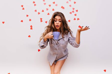 Funny girl with long dark hair posing in studio with cup. Emotional woman looking at mug with coffee.
