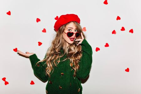 Amazing curly girl touching her sunglasses and expressing amazement in valentines day. Studio shot of surprised european woman in green sweater isolated on white background.