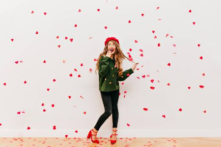 Full-length portrait of amazed long-haired woman in red beret having fun in studio. Trendy girl in black pants expressing positive emotions in valentines day.