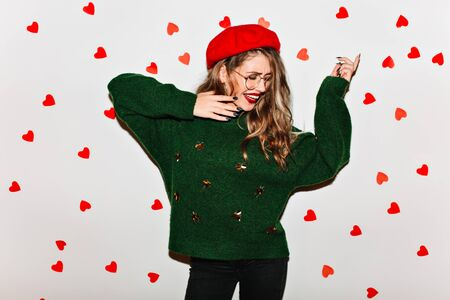 Ecstatic curly woman wears green attire dancing in valentines day. Portrait of dreamy positive girl in red beret fooling around with hearts on background.
