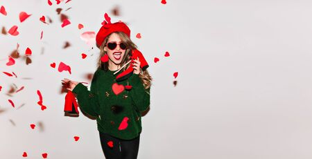 Lovely caucasian girl holding her shoes under heart confetti. Glad curly lady in green sweater enjoying valentines day. Reklamní fotografie
