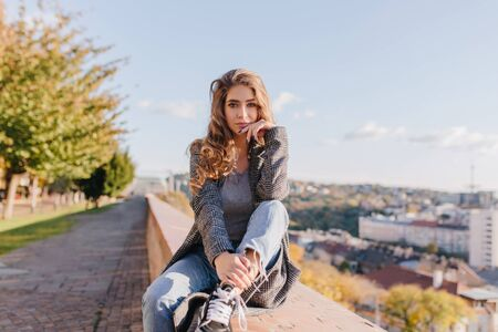Serious well-dressed girl with curly hair propping face with hand. Lovely young woman in blue jeans sitting on pavement on sky background in autumn day. Фото со стока