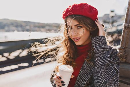 Beautiful girl with big blue eyes posing on the street in cold windy day with cup of coffee. Outdoor photo of long-haired curly woman in french beret spending time in city and drinking latte. Фото со стока