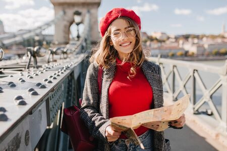 Interested white woman in red sweater and beret spending time outdoor, exploring city with map. Photo of stylish female traveler with backpack enjoying vacation in Europe. Фото со стока
