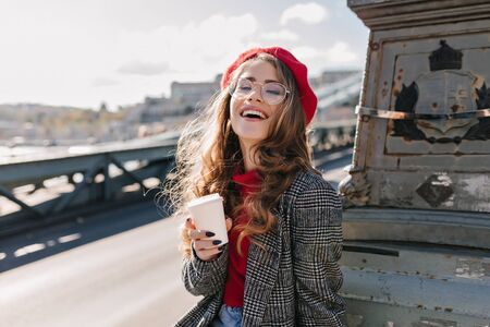 Interested caucasian girl in vintage outfit drinking coffee during trip around Europe. Outdoor photo of cute french lady in red beret enjoying tea while posing in sunny day with sincere laugh. Фото со стока