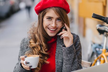 Close-up portrait of lovely french girl with black manicure looking with interested smile. Photo of romantic brown-haired curly woman drinking latte with pleasure on city background. Фото со стока