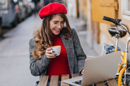 Pretty student in beret looking at laptop screen with interested smile. Outdoor portrait of charming female freelancer enjoying cappuccino and working with computer on the street.