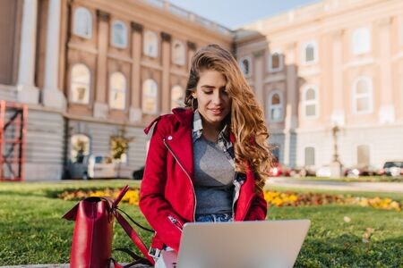 Curious female student in gray sweater sitting on the grass with computer. Charming freelancer with long hair using laptop in park in warm day.