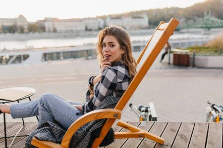 Portrait of resting young woman in checkered shirt posing in comfortable recliner. Outdoot photo of interested white lady in vintage denim pants sitting on chaise-longue on city background. Фото со стока