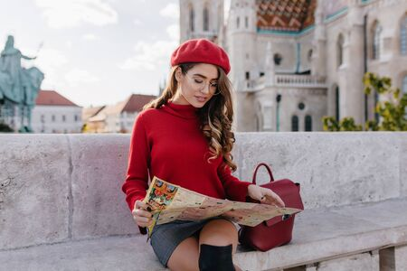 Interested female tourist in knitted sweater looking at map, resting after excursion. Elegant curly girl in red beret sitting beside old palace in autumn day.