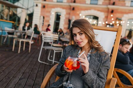 Wonderful brown-haired girl in gray outfit looking with interest while drinking cocktail. Photo of blissful brunette woman in tweed jacket relaxing in outdoor cafe. Фото со стока