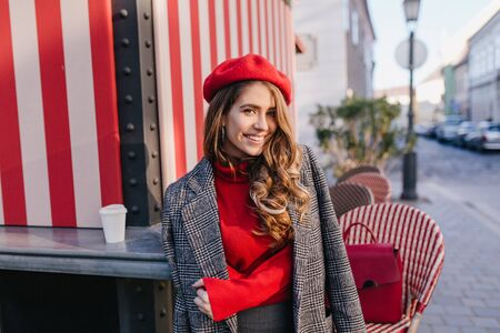 Beautiful white woman in soft coat posing near cafe with striped exterior. Outdoor portrait of pretty caucasian girl wears beret standing with cup of coffee and looking with interested smile.