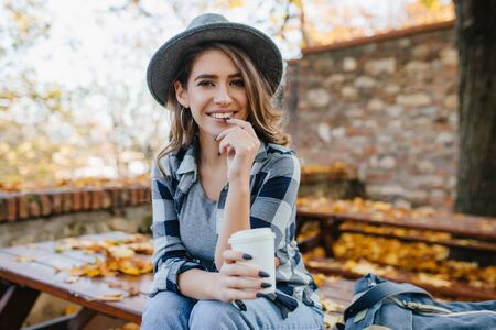 Ecstatic white woman in casual shirt holding cup of tea on blur autumn background. Outdoor photo of interested european lady in hat with long black nails smiling in october weekend. Фото со стока