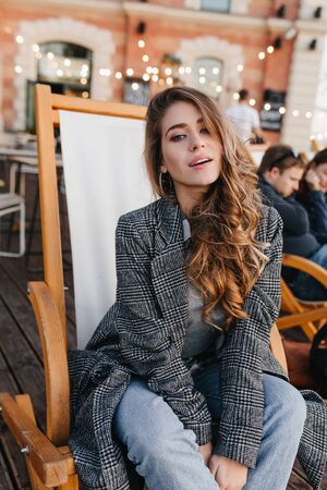 Catching woman with elegant hairstyle sitting on recliner in cafe. Interested white girl in tweed coat posing on comfortable chair in outdoor restaurant. Фото со стока