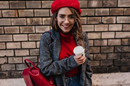 Interested white girl in big glasses looking with smile beside brown brick wall. Outdoor photo of stylish caucasian female model posing with red leather backpack and holding cup of latte.