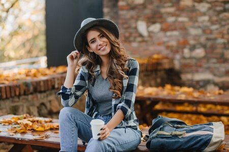 Interested lady with elegant black manicure drinks coffee on wooden bench with golden leaves on background. Outdoor portrait of gorgeous white female model wears hat and casual shirt chilling in park. Фото со стока