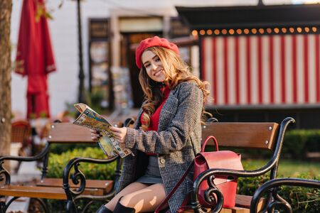 Elegant girl wears skirt and beret sitting on wooden bench in warm autumn day and holding newspaper. Outdoor portrait of cheerful woman reading news in park.