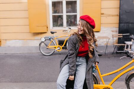 Inspired girl in blue jeans posing on the street and looking around with sincere laugh. Tired smiling woman in beret sitting on yellow bicycle.