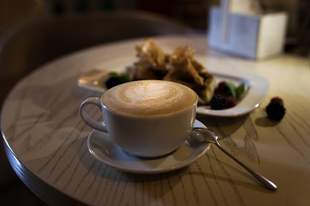 Coffee cappuccino in a coffee cup on wooden table and toast with ice cream. Stock Photo