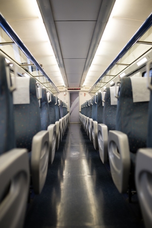 regionally: Empty interior of a passenger train car aka coach or carriage . Rows of unoccupied seats and folding tables in economy or second class.