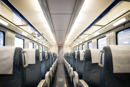 Empty interior of a passenger train car aka coach or carriage . Rows of unoccupied seats and folding tables in economy or second class.