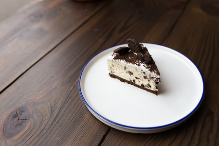 Creamy cheesecake with chocolate chip cookies. On a white plate. On a wooden table.