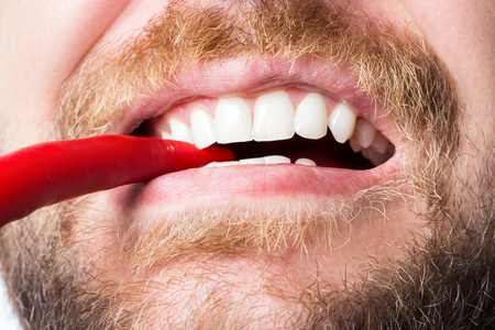 Bearded guy with a snow-white smile bites spicy red pepper