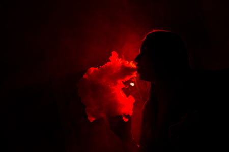 Girl model smokes vape in red light.