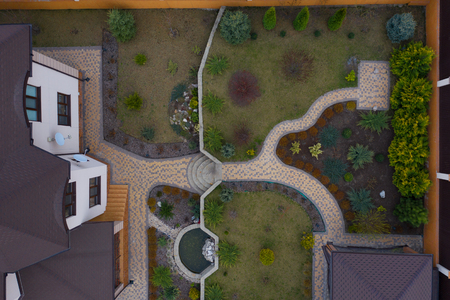 Garden with walkways and green grass. Photo taken from above drone.