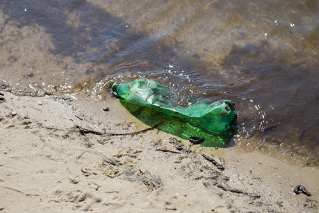 Plastic bottle of green color in a pond on a muddy beach Stok Fotoğraf - 120948926