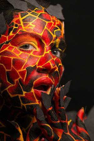 Girl with a painted face on a black background. Body art in the form of a devil