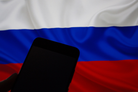 Smartphone in hand without internet connection on the background of the Russian flag Foto de archivo