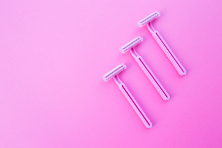 Three womens razors pink color on an isolated pink background. Stock Photo